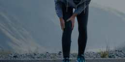 Woman in running outfit holding her knee