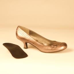 Rose gold heeled shoe next to plantar orthotics
