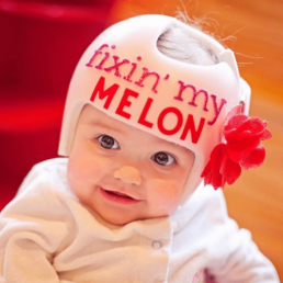 Baby wearing medical helmet that says fixin' my melon with a rose attached